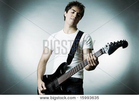 Musiker mit Gitarre auf grauem Hintergrund