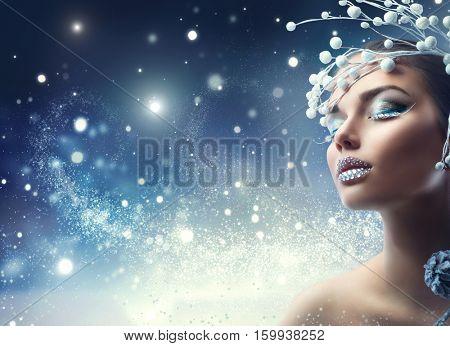 Winter Beauty Woman. Christmas Girl Makeup. Make-up. Beautiful young woman face closeup, winter snow eyelashes and eyeshadow, lips with diamonds