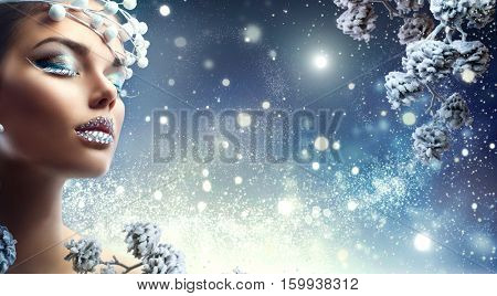 Winter Beauty Woman. Christmas Girl Makeup. Make-up. Beautiful young woman face closeup, winter snow eyelashes and eyeshadow, lips with diamonds