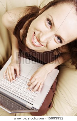 happy young student at home with laptop