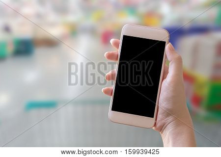 Woman hand holdusing and touch screen smart phone tabletcellphone over blurred people background in supermarket;shopping with copy space