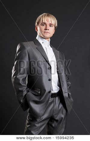 persevering businessman in grey suit standing against dark background
