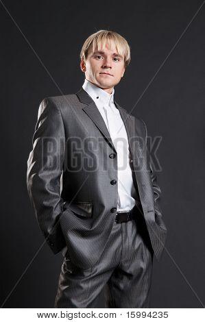 persevering businessman in grey suit standing against dark background