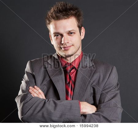 portrait of handsome successful businessman against dark background