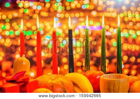 Kwanzaa Celebration Concept With Seven Candles Red, Black And Green, Gift Box, Pumpkin, Bowl And Fru