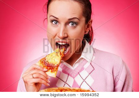 funny woman eating pizza against pink background