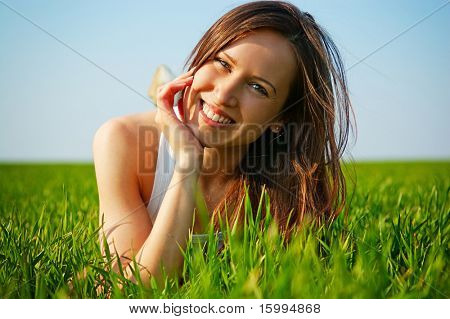 sunny picture of attractive young woman lying in green grass