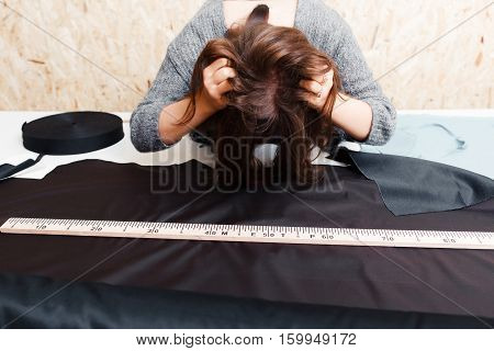 Stressed woman tailor tousle her hair on workplace. Pattern cutting designer getting crazy above table with black fabric. Overwork, troubles, difficult order concept