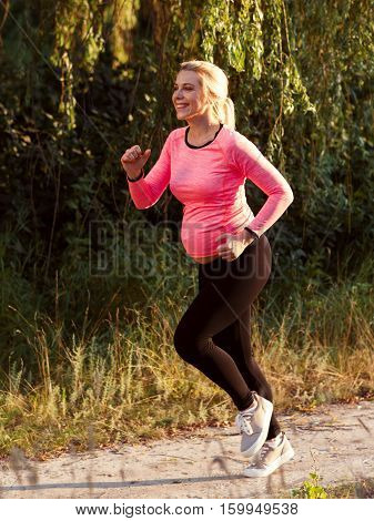 Happy pregnant woman jogging outside. Smiling expectant blonde running in forest. Sport, pregnancy, healthy lifestyle concept