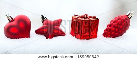 Christmas holiday decorations, red heart, pine cone and gift in the snow on white panoramic banner background