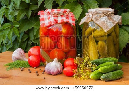 Canned And Fresh Vegetables. Canned Tomatoes And Pickled Cucumbers In Glass Jars On Wooden Table Outdoor. Homemade Canned Vegetables.