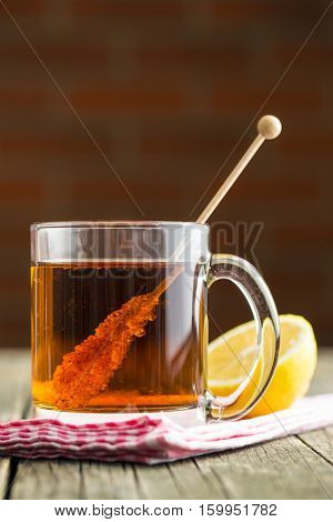 Tea cup with sugar crystal on wooden stick on old wooden table.