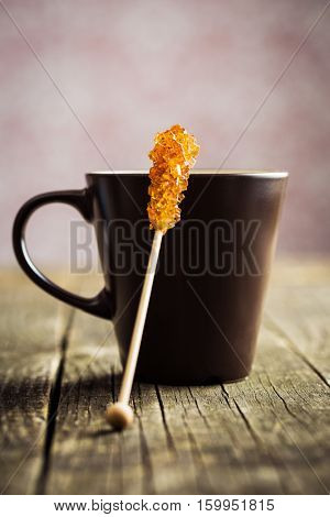 Brown amber sugar crystal on wooden stick and coffee cup on old wooden table.