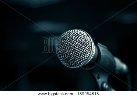 Microphone with metal body in holder on blur background. Close-up selected focus