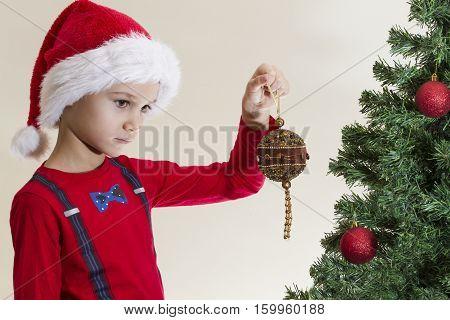 Sad boy in Santa cap looking at Christmas tree with xmas toy at home