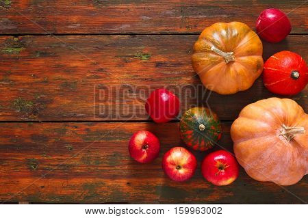 Autumn harvest background. Various pumpkins and red apples border on weathered rustic red wood with copy space. Top view, still life. Healthy vegetable food, organic farming concept