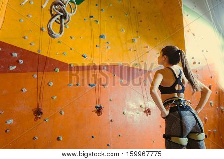 I am ready. Young pretty active woman wearing sportswear and standing in a climbing gym waiting for her climb.