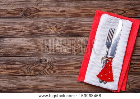 Christmas table place setting with fork and knife, decorated christmas toy - red fir-tree. Christmas holidays background.