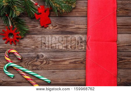 Christmas table place setting, decorated christmas pine branches with christmas toys, two lollipop cane and red napkin. Christmas holidays background.