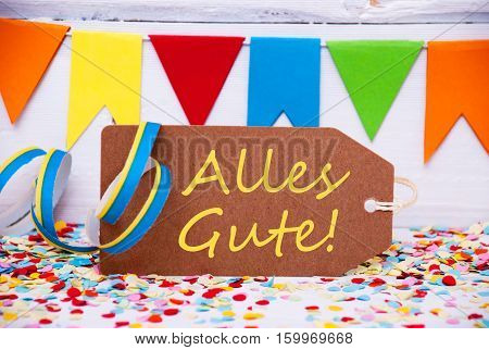 Brown Label With German Text Alles Gute Means Best Wishes. Party Decoration Like Streamer And Confetti. White Wooden Background. Greeting Card For Celebrations