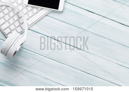 Headphones, phone and pc on wooden desk table. Music concept. Top view with copy space