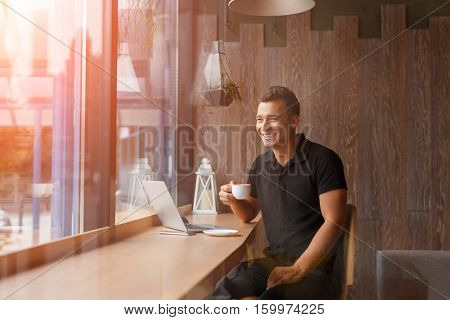 Handsome young freelancer is having a coffee break and dreaming with a laptop