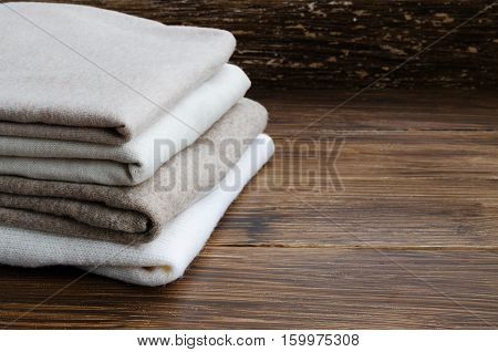 Stack of knitted clothes in nude beige tones. Sweaters and cardigan on a wooden background. Concept of Winter time and Christmas holiday. Copy space.