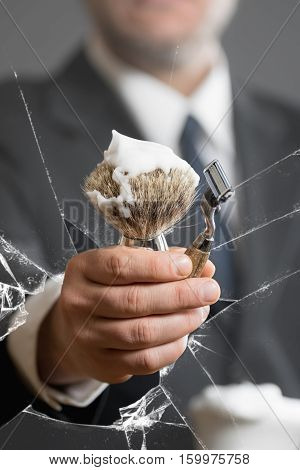 Business Man with Shaving Tool behind a broken Glass Pane