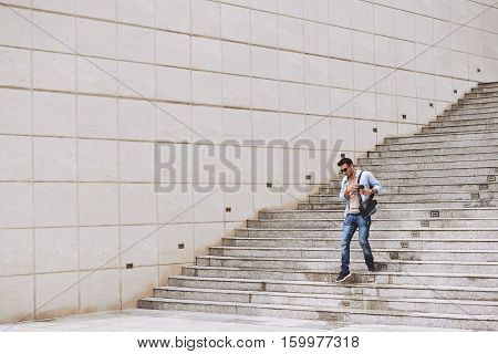 Young man going down the stairs outdoors