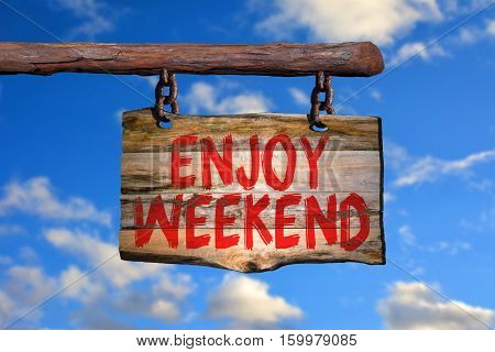 Enjoy weekend motivational phrase sign on old wood with blurred background