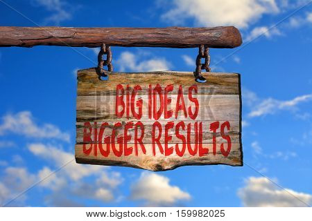 Big ideas bigger results motivational phrase sign on old wood with blurred background