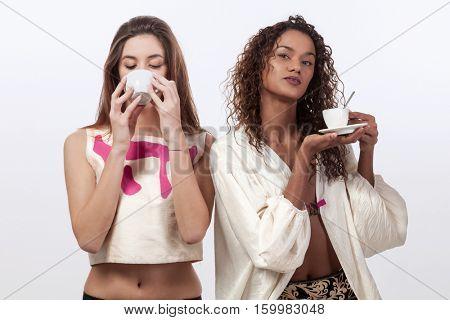 Two young women drinking coffee, studio portrait