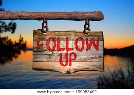 Follow up motivational phrase sign on old wood with blurred background
