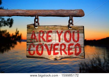 Are you covered motivational phrase sign on old wood