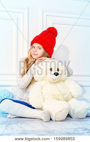 Cute little 7 year old girl wearing knitted winter clothes posing with her teddy bear. Children's fashion. White interior.