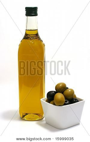 gold olive oil with black and green olives in white ceramic bowl