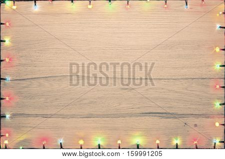 Christmas lights of different colors frame on a wood