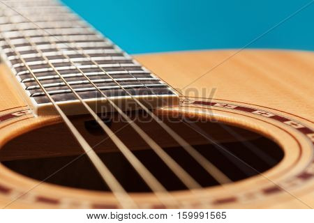 Classic fcoustic guitar on blue background upclose