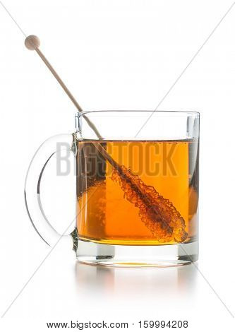 Tea cup with sugar crystal on wooden stick isolated on white background.