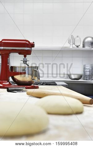 Closeup of dough on wooden board beside dough mixer in kitchen