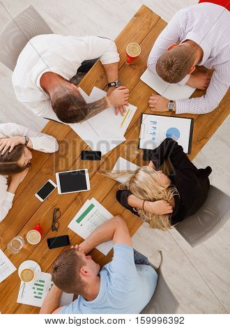 Overworking concept. Group of business people exhausted sleep in office, top view of wooden table with mobile devices. Men and women team tired and relaxed after overtime brainstorm