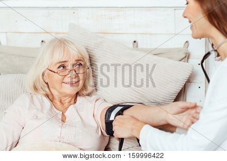 Check it out. Pleasant elderly positive woma lying in bed while professioanl doctor measuring her blood pressure while visiting her patient at home