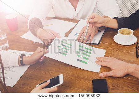 Business meeting. Hands closeup at modern office workplace, wooden desk and coffee cups on it. Team discussion, data analysing, show information on papers with diagram. Brainstorming with partners