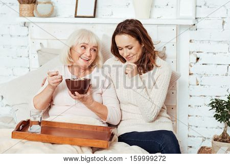 Happy family. Pleasant delighted elderly woman lying in bed and enjoyign her breakfast while positive granddaughter taking care of her