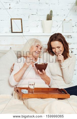 Happy time together. Pleasant delighted young woman taking care of her grandmother while sitting with her in bed and talking