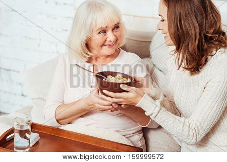 Thats for you. Pleasant young cheerful woman giving breakfast to her grandmother and taking care of her while expressing gladness