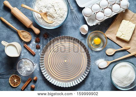 Baking cake in kitchen - dough recipe ingredients eggs, flour, milk, butter, sugar on table from above. Bake sweet cake dessert concept. Top view.