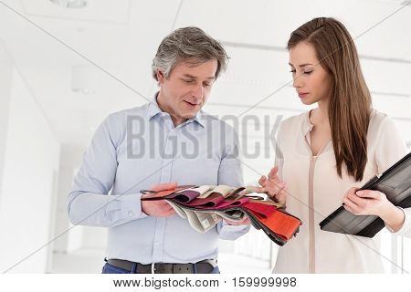 Businesswoman and businessman discussing over cloth swatches in new office