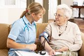 Senior Woman Ihaving Blood Pressure Taken By Health Visitor At Home