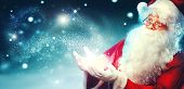 Santa Claus with magic gift in his hands. Portrait of happy Santa Claus making magic at night, Blowi poster